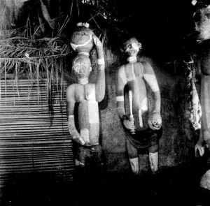 Figures in Obu house. Female with pot on head, male with cutlass and trophy head, Abiriba